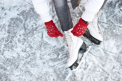 Girl tying shoelaces on ice skates before skating on the ice rink, hands in red knitted gloves. View from top.