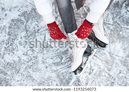 Girl tying shoelaces on ice skates before skating on the ice rink, hands in red knitted gloves. View from top. - Shutterstock ID 1193256073