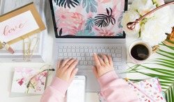 Girl typing on laptop in bright colourful office with pink and chic accessories