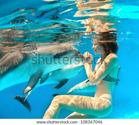 Girl under the water touches the dolphin