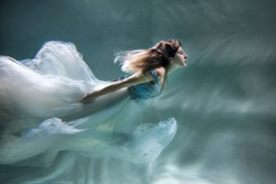girl under water as an angel .in a beautiful light dress. floats like a mermaid
