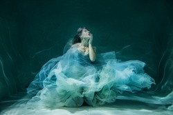 Girl under water in a chic wedding dress. like a jellyfish