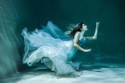 Girl under water in a chic wedding dress. like a mermaid