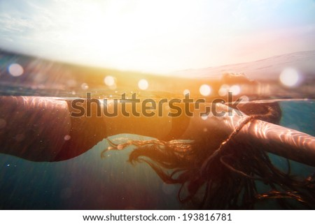 Girl underwater with sun rays. vintage retro style with soft focus, bokeh and sun flare #193816781