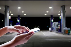 Girl use mobile phone ,blur image of gas station as background.