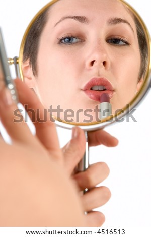 Girl uses lipstick (view through reflection in mirror)