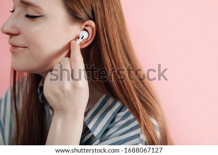 girl uses wireless white headphones on a pink background. Air Pods Pro. EarPods New Airpods pro on pink background. Airpodspro. female headphones.EarPods