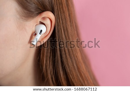 girl uses wireless white headphones on a pink background. Air Pods Pro. with Wireless Charging Case. New Airpods pro on pink background. Airpodspro. female headphones. apple headphones.EarPods