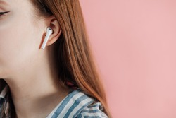 girl uses wireless white headphones on a pink background. Air Pods. with Wireless Charging Case. New Airpods on pink background. Airpods. female headphones. apple headphones.