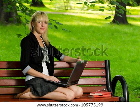 Girl using a laptop studying for the exam in the park