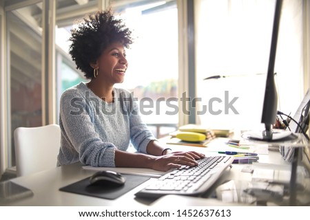 Girl using her computer, sitting on the desk #1452637613