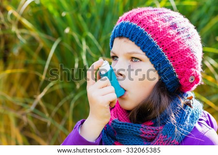 Girl Using Inhaler on an autumn day - to Treat Asthma Attack. Inhalation treatment of respiratory diseases. Shallow depth of field. Allergy concept. Asthma child
