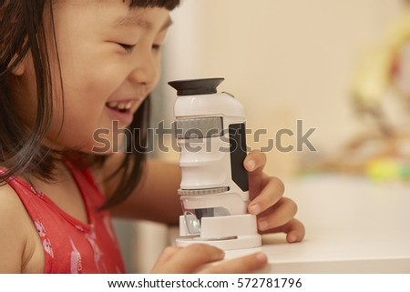 Girl using microscope at home or classroom. Curiosity is the key of successful learning experience in early childhood education. #572781796