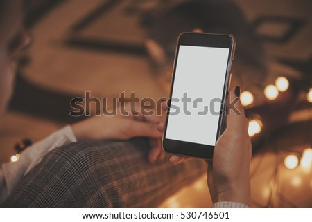 Girl using mobile phone in a home atmosphere - hipster look with blank space.
