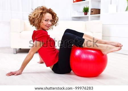 Girl using red fitness ball at home