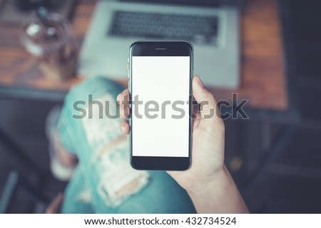 Shutterstock girl using smart phone in cafe. hand holding smart phone white screen. black color smart phone vintage tone. hand holding using mobile phone.