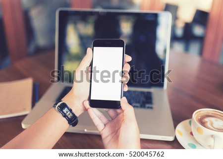 girl using smart phone in cafe. hand holding smart phone white screen. black color smart phone vintage tone. hand holding using mobile phone in coffee shop