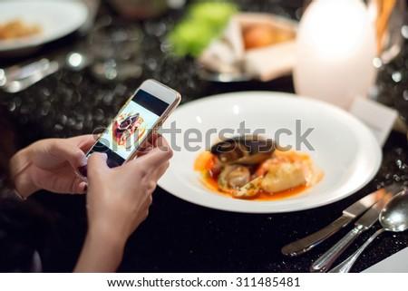 girl Using Smart phone taking her italian seafood dish