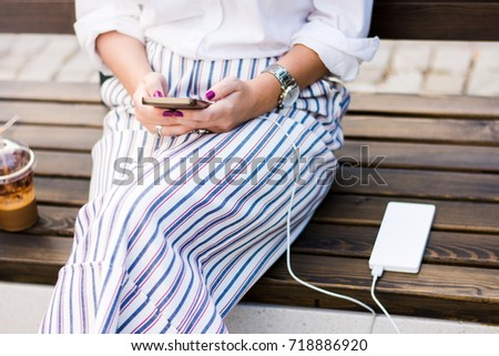 Girl using smart phone while charging on the power bank
