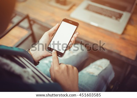girl using smartphone in cafe. smartphone white screen. hand holding smartphone. black color smartphone on vintage tone.