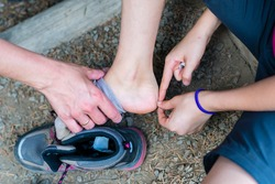 Girl using sticking plaster due to tight shoes during mountain trip