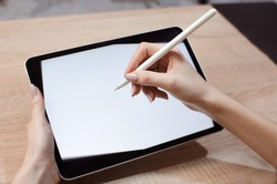 Girl using stylus on tablet to draw her ideas