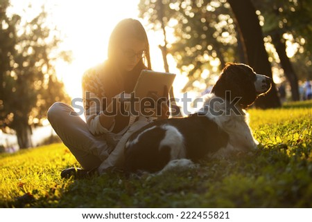 Girl Using Tablet In The Park On The Grass With The Dog At Sunset #222455821