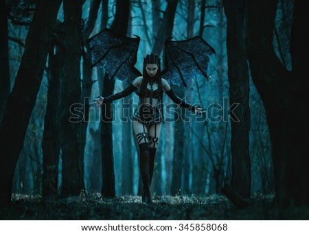 Stock Photo Girl vampire, a demon with bat wings, a succubus,through the dark forest girl walking a bat with huge wings and sexy outfit,fashionable toning,creative computer colors