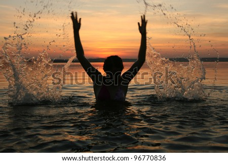 girl very splashing in the water at the beach creating many splashes over their heads against the backdrop of setting sun