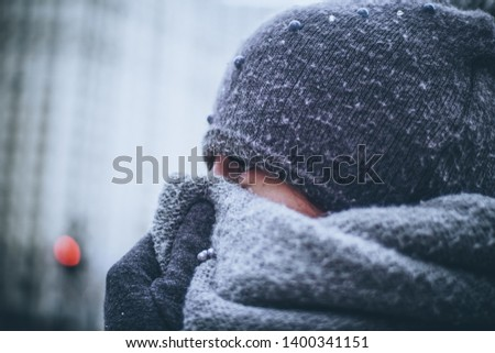 Girl very warmly dressed during a cold winter day covers her face with a thick scarf because really low temperatures outside. Photo take in Chicago during extremely cold and freezing winter day.