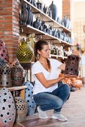 Girl visiting souvenir shop and choosing earthenware