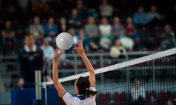 Girl Volleyball player and setter setting the ball for a spiker during a game