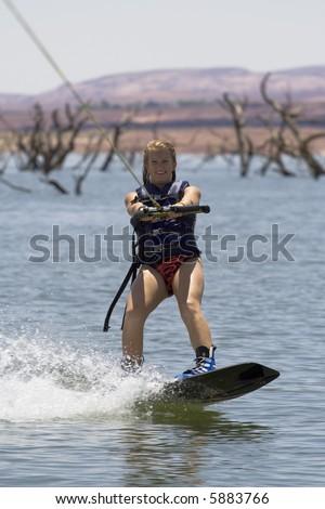 Girl wakeboarding at Lake Powell in Glen Canyon National Recreation Area Utah - stock photo