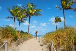 Girl waking  to the beach. Footpath with palm trees, and ocean in the background.South Beach, Miami, Florida, USA