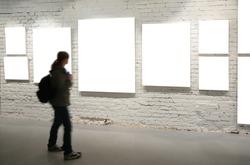 Girl walk through frames on a brick wall