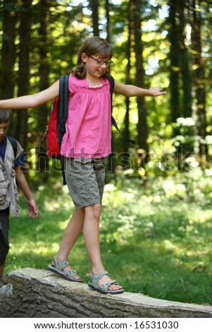 Girl walking across log