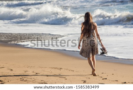 girl walking alone bare foot at the beach in a Greek island during sunny day