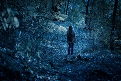 Girl walking alone on path in mystic dark forest. Lonely woman in strange creepy park at night in autumn. Young woman in fantasy spooky woods in twilight. Fear in scary mystery forest on Halloween.