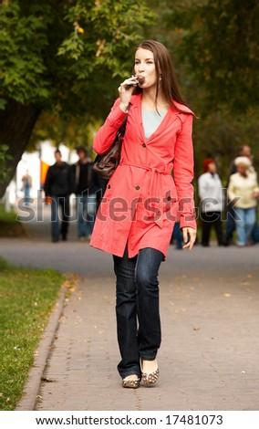 Girl walking along footpath and eating chocolate ice-cream