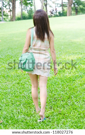 girl walking away in park