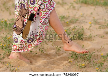 Girl walking barefoot on a dune with spring colours