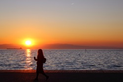Girl walking by a subset near the sea