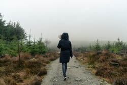 Girl walking down a misty pathway through the forests in the Wicklow mountains in Ireland