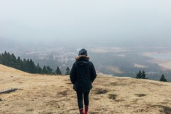 Girl walking down mountain in fall, with cloudy, foggy sky overlooking the town of Banff.