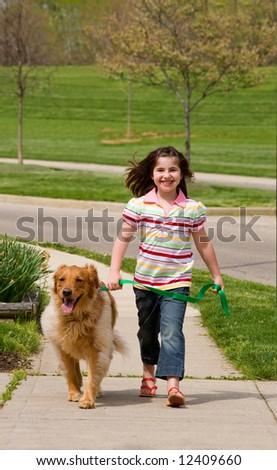 Girl Walking Down the Sidewalk With Dog - stock photo