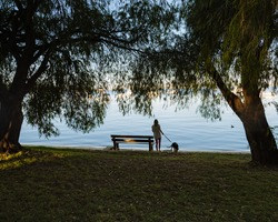 Girl walking her dog at Matilda Bay reserve at sunrise. Beautiful calm morning with no wind or clouds.