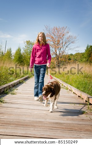 girl walking her dog on a boardwalk