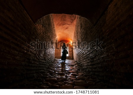 girl walking in a tunnel with a window in the background. Long tunnel. death Photo stock ©