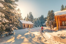 Girl walking in snowy forest meets with village houses. Snow covered trees and winter landscape. View of snow on a sunny day. Uludag National Park, Bursa, Turkey