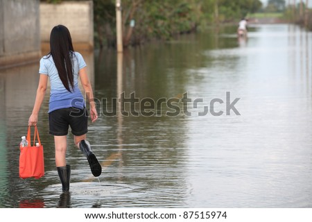 girl walking on flooded street,carrying fresh water for drinking.